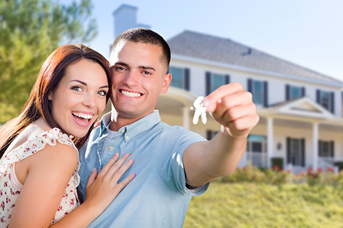 happy couple with keys in front of new house